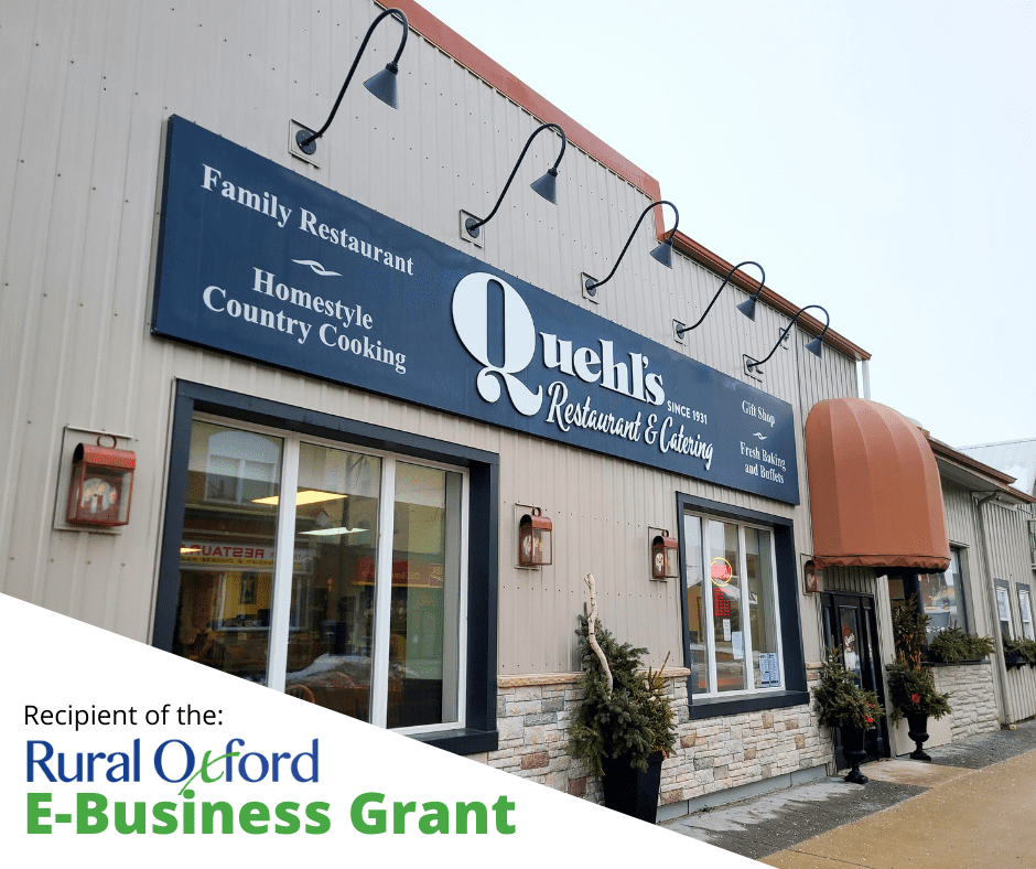front façade of Quehl's Restaurant & Catering with seasonal arrangements in urn on pavement and Recipient of Rural Oxford E-Business Grant logo
