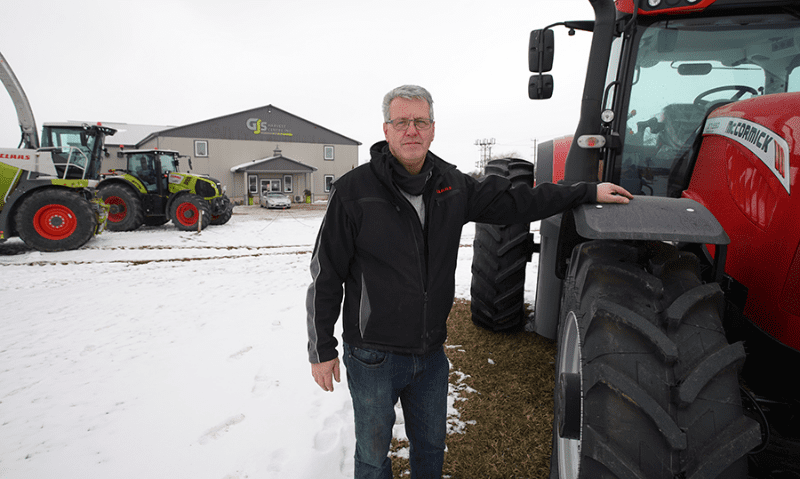 Gary Klyn standing in snow with hand on tractor fender outside GJ's Harvest Centre