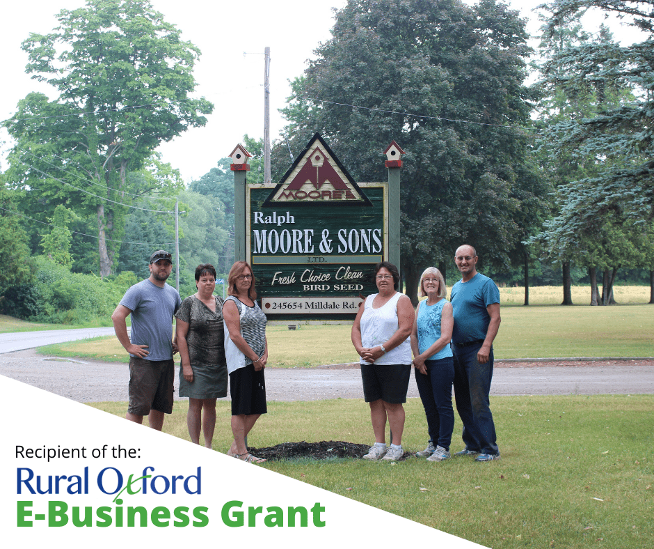 Wilson family gathered around their Ralph Moore & Sons sign at the farm entrance, Recipient of the Rural Oxford E-Business Grant in bottom left of image