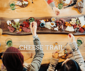 Charcuterie board on wood table with hands reaching in to partake of cheeses