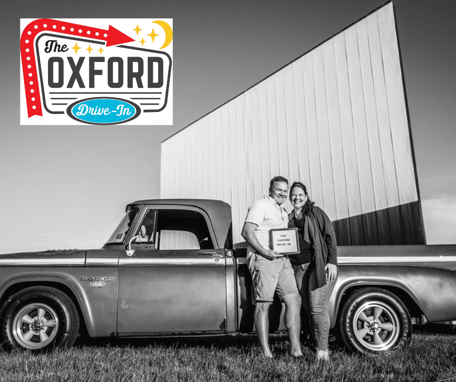 Black and white photo with Owners of The Oxford Drive-In posed with vintage truck in front of drive-in screen and Drive-In logo
