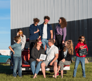 Owners and family posed on tailgate of vintage truck in front of screen