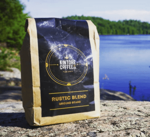 Bag of Kintore Coffee on large rock with blue lake in background