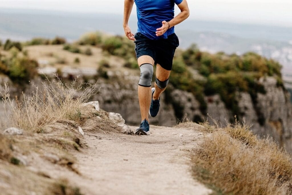 Person running on trail with knee brace